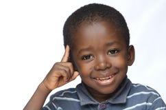 El pequeño muchacho africano que pensaba con el finger señaló en su cabeza aislada en blanco Foto de archivo libre de regalías