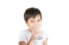 El pequeño muchacho asiático bebe el agua de un vidrio en el fondo blanco Imagenes de archivo
