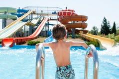 El pequeño muchacho caucásico sano cerca de la piscina azul en agua del verano parquea al aire libre Imagen de archivo