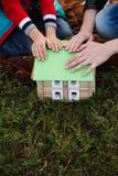 El pequeño muchacho con su madre montó a un diseñador de madera de la casa, puso Fotografía de archivo libre de regalías