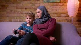 El pequeño muchacho concentrado que juega el videojuego con la palanca de mando y a su madre musulmán en hijab le ayuda a ganar e almacen de video