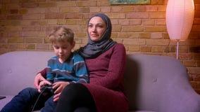 El pequeño muchacho concentrado que juega el videojuego y a su madre musulmán en hijab intenta coger la palanca de mando para int almacen de metraje de vídeo