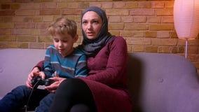 El pequeño muchacho concentrado que juega el videojuego y a su madre musulmán en hijab toma la palanca de mando e intenta ayudarl metrajes