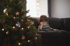 El pequeño muchacho de pelo largo está mirando un vídeo en el teléfono que se sienta en el sofá por el árbol de navidad Un niño q fotos de archivo