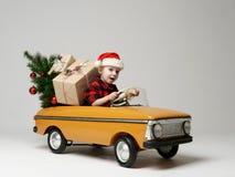 El pequeño muchacho del niño en el invierno que se sienta en un coche retro amarillo del juguete tira en el árbol de navidad ador Imagen de archivo libre de regalías