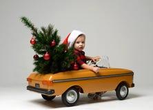 El pequeño muchacho del niño en el invierno que se sienta en un coche retro amarillo del juguete tira en el árbol de navidad ador Imagenes de archivo