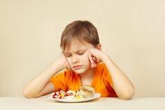 El pequeño muchacho descontentado no quiere comer las pastas con la chuleta imagen de archivo libre de regalías