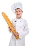 El pequeño muchacho divertido se vistió en uniforme del cocinero con el baguette fresco Fotos de archivo