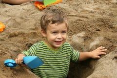 El pequeño muchacho en excavado enarena el agujero Imagen de archivo