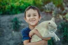El pequeño muchacho es cuidado sobre su gato imagenes de archivo