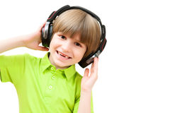 El pequeño muchacho está escuchando la música Imagen de archivo