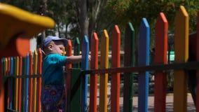 El pequeño muchacho está permaneciendo cerca de la cerca del colorfulrainbow en la cámara lenta metrajes