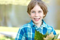 El pequeño muchacho feliz con caída se va sobre fondo de la naturaleza fotos de archivo