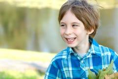 El pequeño muchacho feliz con caída se va sobre fondo soleado de la naturaleza, fotos de archivo libres de regalías