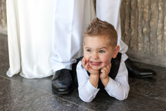 El pequeño muchacho feliz miente en un piso en una boda Fotografía de archivo
