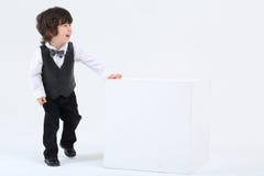 El pequeño muchacho feliz se coloca cerca del cubo grande y ríe en la parte posterior del blanco Imagenes de archivo