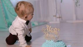 El pequeño muchacho hermoso lindo está jugando con la primera torta que se sienta en el piso almacen de video