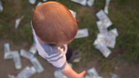 El pequeño muchacho lanza cientos billetes de dólar alrededor de él en la cámara lenta, visión desde arriba almacen de metraje de vídeo