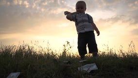 El pequeño muchacho lanza feliz una pila enorme de billetes de dólar a la tierra, cámara lenta metrajes