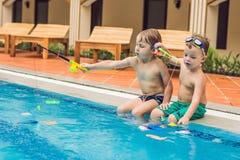 El pequeño muchacho lindo dos está cogiendo un pescado del juguete en la piscina Fotografía de archivo libre de regalías