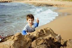 El pequeño muchacho lindo en costa de mar manosea con los dedos encima de jugar con las rocas Fotografía de archivo libre de regalías
