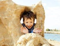 El pequeño muchacho lindo en costa de mar manosea con los dedos encima de jugar con las rocas Imagen de archivo