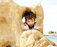 El pequeño muchacho lindo en costa de mar manosea con los dedos encima de jugar con las rocas Imágenes de archivo libres de regalías