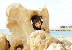 El pequeño muchacho lindo en costa de mar manosea con los dedos encima de jugar con las rocas Foto de archivo libre de regalías