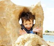 El pequeño muchacho lindo en costa de mar manosea con los dedos encima de jugar con las rocas, lifes Fotografía de archivo