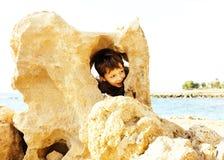El pequeño muchacho lindo en costa de mar manosea con los dedos encima de jugar con las rocas Imagen de archivo libre de regalías