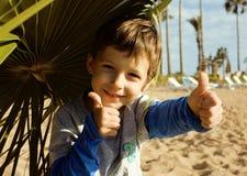 El pequeño muchacho lindo en costa de mar manosea con los dedos para arriba Imagenes de archivo