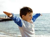 El pequeño muchacho lindo en costa de mar manosea con los dedos para arriba Imagen de archivo libre de regalías