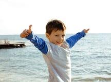 El pequeño muchacho lindo en costa de mar manosea con los dedos para arriba Fotografía de archivo libre de regalías