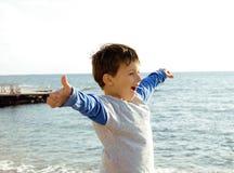 El pequeño muchacho lindo en costa de mar manosea con los dedos para arriba Fotografía de archivo