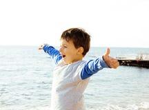 El pequeño muchacho lindo en costa de mar manosea con los dedos para arriba Foto de archivo libre de regalías