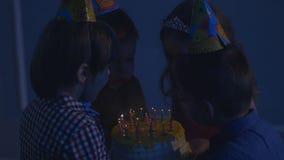 El pequeño muchacho lindo sopla hacia fuera la vela en la torta y las palmadas y otros niños lo miran los niños van de fiesta en  almacen de video
