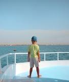 El pequeño muchacho mira horizonte en el barco de vela Fotografía de archivo