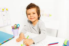 El pequeño muchacho positivo dibuja con el lápiz durante el ABA Fotografía de archivo
