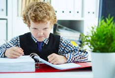 El pequeño muchacho rizado enojado le gusta el hombre de negocios que hace papeleo en oficina imagenes de archivo