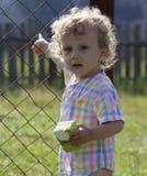 El pequeño muchacho rizado se coloca cerca de una cerca metálica Fotografía de archivo