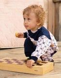 El pequeño muchacho rizado sostiene un tablero de ajedrez Fotos de archivo libres de regalías
