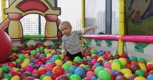 El pequeño muchacho rubio camina en la piscina con las bolas plásticas en el cuarto de niños almacen de video