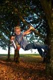 El pequeño muchacho rubio está colgando en el árbol con la cartera imagenes de archivo