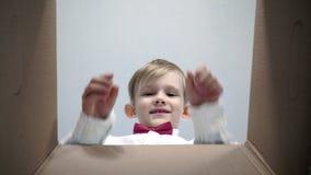 El pequeño muchacho rubio feliz en una camisa blanca con una corbata de lazo roja parece en la caja, es sorprendido y feliz recib almacen de video