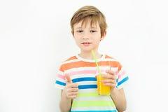 El pequeño muchacho rubio va a beber un zumo de naranja fresco Imagenes de archivo