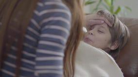 El pequeño muchacho se acuesta en sofá debajo de la manta y de la muchacha que tocan su frente con la mano para ver si el hermano almacen de video