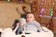 El pequeño muchacho se sienta en una maleta con un juguete en el cuarto con Christm Fotografía de archivo libre de regalías