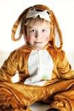 El pequeño muchacho se vistió para el conejito que se sentaba en la tierra imagenes de archivo