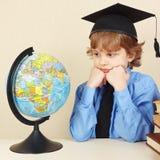 El pequeño muchacho serio en sombrero académico mira el globo Imagen de archivo libre de regalías