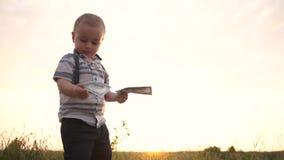 El pequeño muchacho serio lanza una pila enorme de billetes de dólar a la tierra, cámara lenta almacen de metraje de vídeo